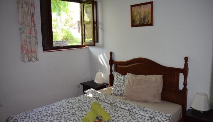 Schlafzimmer in Casa La Solina mit Doppelbett und Blick in den Garten