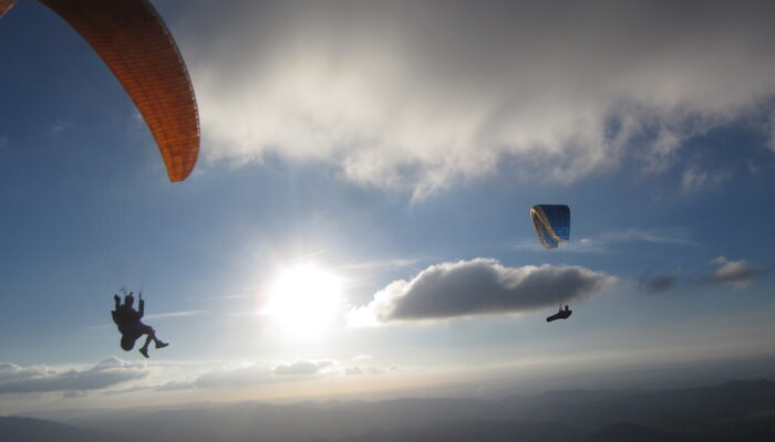 Two paragliders soaring in front of the sun and clouds