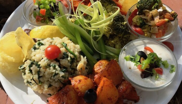 A tapas plate with rice, potatoes, fried veggies and a selection of raw goodness, with a portion of our famous Aioli.