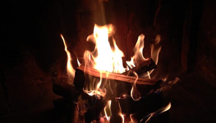 A warming photo of logs of wood burning away in the open fireplace